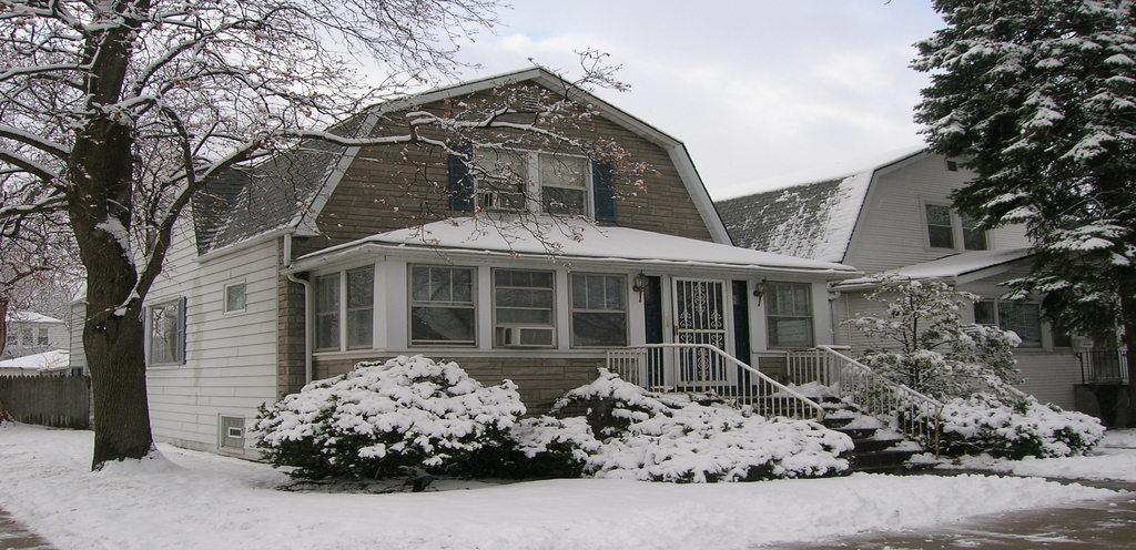 A cream and tan house covered in snow with bushes and trees out in the front yard of the home